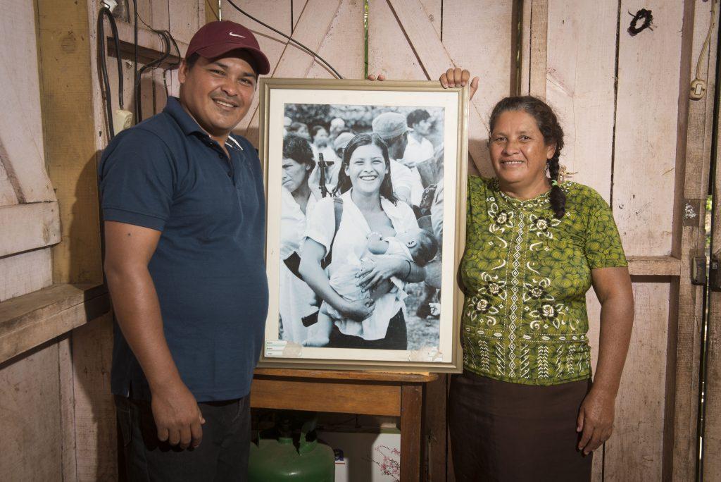 """Blanca López Hernández posa con su hijo José Antonio López Pérez y la fotografía de """"la miliciana de Waswalito"""" en la que ambos aparecen."""